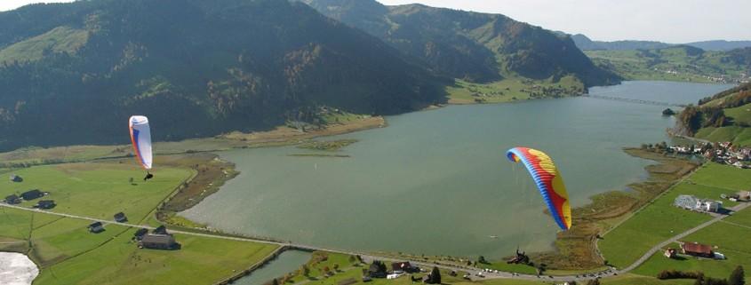 Zwei Hochleister-Gleitschirme soaren im kleinen und feinen Fluggebiet Euthal am Sihlsee.